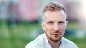 Nahaufnahmeporträt des hübschen überzeugten jungen Mannes, der die Kamera nachdenklich betrachten im Freien aufwirft stock video
