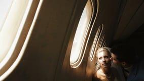 Nahaufnahmeporträt des hübschen Bräutigams, der seine reizend Braut in der Backe beim Sitzen nahe dem Fenster in küsst stock video