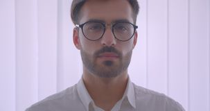 Nahaufnahmeporträt des hübschen erfolgreichen kaukasischen Geschäftsmannes in den Brillen, die Kamera im Weiß drehen und betracht stock footage