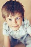 Nahaufnahmeporträt des hübschen lächelnden kleinen Jungen mit braunen Augen lizenzfreie stockfotos