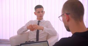 Nahaufnahmeporträt des jungen attraktiven Geschäftsmannes, der ein Gespräch mit seinem Partner unter Verwendung des Laptops im Bü stock footage