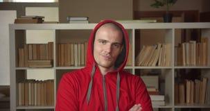 Nahaufnahmeporträt des jungen attraktiven kaukasischen männlichen Studenten, der auf seine Haube sich setzt und im Vertrauen läch stock footage