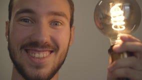 Nahaufnahmeporträt des jungen bärtigen Mannes drehen sich auf anf weg von der elektrischen Weinlesebirne und dem Lächeln mit dem  stock video