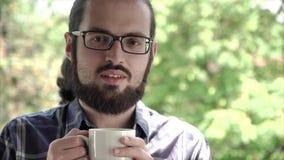 Nahaufnahmeporträt des jungen Büromannes genießen das Riechen einer Schale frischen Kaffees stock video