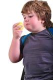Nahaufnahmeporträt des Jungen einen Apfel essend Stockbilder