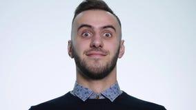 Nahaufnahmeporträt des jungen Gesichtes des gutaussehenden Mannes, das Erstaunen und Bewunderung im Studio auf weißem Hintergrund stock video footage