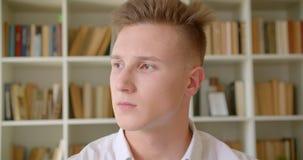 Nahaufnahmeporträt des jungen hübschen kaukasischen Studenten, der Kamera in der Collegebibliothek betrachtet stock footage