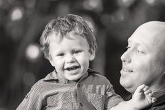 Nahaufnahmeporträt des jungen hübschen Vaters und kleinen lachenden des Sohns im Freien am Sommertag Schwarzweiss-Foto Pekings, C Lizenzfreie Stockfotografie
