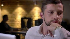 Nahaufnahmeporträt des jungen kaukasischen Geschäftsmannes, der denkt und vor dem Laptop im Büro konzentriert wird stock video