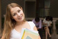 Nahaufnahmeporträt des jungen Mädchens mit den Büchern im Freien stockfotografie