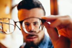 Nahaufnahmeporträt des jungen Mannes mit Gläsern, der Sehvermögenprobleme hat lizenzfreie stockbilder
