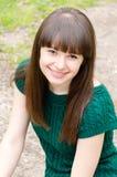 Nahaufnahmeporträt des jungen Schönheit Brunettemädchens, das draußen glückliche lächelnde u. schauende Kamera sitzt Stockfotos