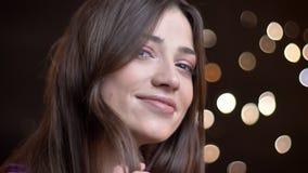 Nahaufnahmeporträt des kaukasischen brunette Mädchens, das faszinierend in Kamera auf unscharfem Lichthintergrund aufpasst stockfoto