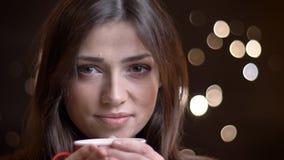 Nahaufnahmeporträt des kaukasischen brunette Mädchens mit Tasse Kaffee ruhig aufpassend in Kamera auf unscharfem Lichthintergrund lizenzfreie stockfotos