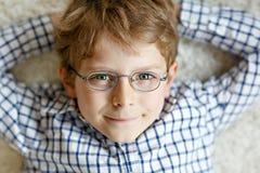 Nahaufnahmeporträt des kleinen blonden Kinderjungen mit braunen Brillen stockfotos