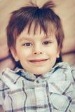 Nahaufnahmeporträt des lächelnden kleinen Jungen mit braunen Augen lizenzfreie stockfotos
