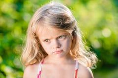 Nahaufnahmeporträt des launischen blonden kleinen Mädchens mit den geschürzten Lippen Stockbild
