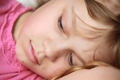 Nahaufnahmeporträt des liegenden kleinen blonden Mädchens Lizenzfreie Stockfotos