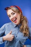 Nahaufnahmeporträt des lustigen emotionalen Mädchens, das Daumen oben auf Querstation zeigt Lizenzfreie Stockfotos
