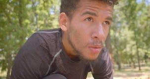 Nahaufnahmeporträt des männlichen Rüttlers des jungen athletischen Afroamerikaners, der sich vorbereitet, in den Park zu laufen d stock footage