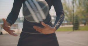 Nahaufnahmeporträt des männlichen Trainings des sportlichen Afroamerikaners Handmit einem Basketballball auf dem Gericht in der s stock video footage