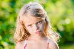 Nahaufnahmeporträt des missfallenen kleinen Mädchens mit den geschürzten Lippen Lizenzfreies Stockfoto