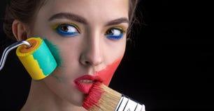 Nahaufnahmeporträt des Modells mit Farbenrolle und -bürste stockfoto