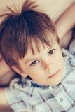 Nahaufnahmeporträt des nachdenklichen kleinen Jungen mit braunen Augen stockbild