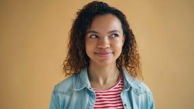 Nahaufnahmeporträt des netten Afroamerikanermädchens, das ihre Augen und Lächeln rollt stock video footage