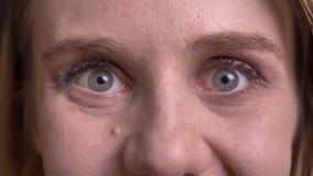 Nahaufnahmeporträt des netten blonden hervorstehenden Modells ihre Augen in der positiven Unterhaltung auf schwarzem Hintergrund stock video footage