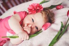 Nahaufnahmeporträt des netten lächelnden Babys, das sich in der Hand auf rosa Bett mit Tulpe hinlegt Betrachten der Kamera und Ze lizenzfreies stockbild