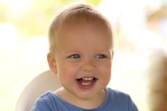 Nahaufnahmeporträt des netten Säuglingskindes, das Kamera lacht und betrachtet Lizenzfreies Stockfoto