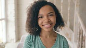 Nahaufnahmeporträt des schönen Afroamerikanermädchens, das Kamera lacht und untersucht Jugendlichshowgefühle von den serios stock video footage