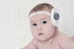 Nahaufnahmeporträt des schönen Babys mit Blume Lizenzfreies Stockfoto