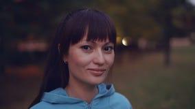 Nahaufnahmeporträt des schönen Brunette mit dem Pferdeschwanz, der den hellen Kapuzenpulli betrachtet Kamera und die lächelnde St stock footage