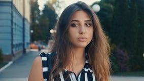 Nahaufnahmeporträt des schönen brunette Modells der jungen Frau, welches die Kamera auf einem Stadtstraßenhintergrund betrachtet  stock footage