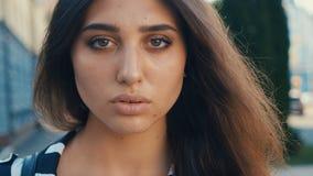 Nahaufnahmeporträt des schönen brunette Modells der jungen Frau, welches die Kamera auf einem Stadtstraßenhintergrund betrachtet  stock video footage