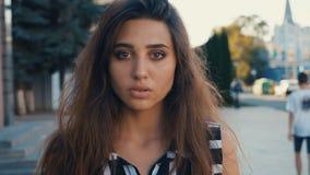 Nahaufnahmeporträt des schönen brunette Modells der jungen Frau, welches die Kamera auf einem Stadtstraßenhintergrund betrachtet  stock video