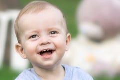 Nahaufnahmeporträt des schönen kleinen Babys, das zur Kamera Sommertag lacht und betrachtet Unscharfer Hintergrund Lizenzfreie Stockfotografie