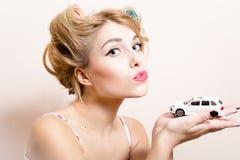 Nahaufnahmeporträt des schönen lustigen blonden Pinupmädchens mit den grünen Augen u. Lockenwicklern, die mit Auto in den Händen s Stockfotografie