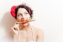 Nahaufnahmeporträt des schönen reizend jungen Brunettefrauenpin-up-girl beißt Pinsel u. oben schauen auf weißem Hintergrund Stockfotografie