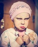 Nahaufnahmeporträt des traurigen kleinen Mädchens mit den geschürzten Lippen Stockbild