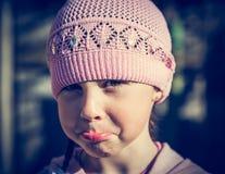 Nahaufnahmeporträt des traurigen kleinen Mädchens mit den geschürzten Lippen Stockbilder