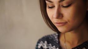 Nahaufnahmeporträt des trinkenden Tees der jungen attraktiven Schönheit mit Zitrone, ihr Haar berührend und beiseite schauen stock video