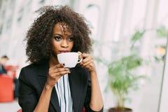 Nahaufnahmeporträt des trinkenden Tees des schönen afroen-amerikanisch Mädchens im Café stockbild