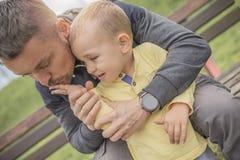Nahaufnahmeporträt des Vaters und des schreienden Kindes im Park stockfotografie