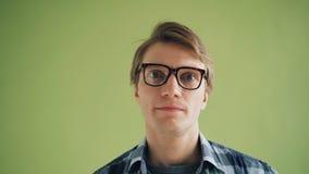 Nahaufnahmeporträt des verwirrten jungen Mannes, der seine Augen tragen Gläser rollt stock video