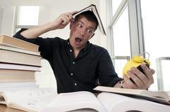 Nahaufnahmeporträt des weißen Mannes umgeben durch Tonnen Bücher, Wecker, betont vom Projekttermin, Studie, Prüfungen Stockfoto