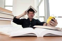 Nahaufnahmeporträt des weißen Mannes umgeben durch Tonnen Bücher, Wecker, betont vom Projekttermin, Studie, Prüfungen Stockfotografie