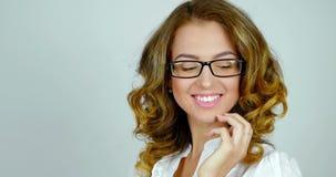 Nahaufnahmeporträt einer attraktiven jungen Frau in den Gläsern wirft auf und lächelt in einem Studio stock footage